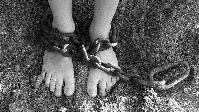 足を鎖で縛られている